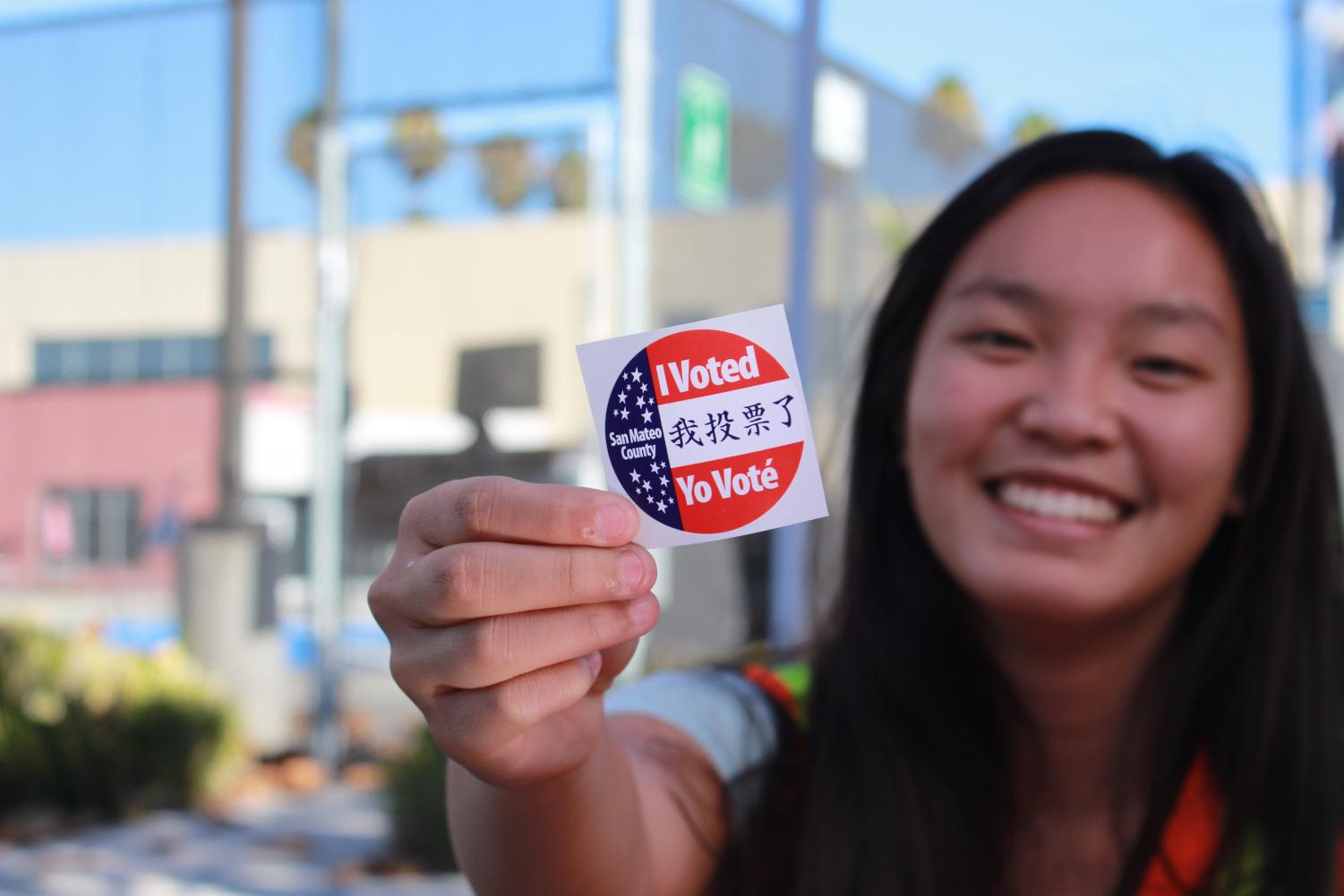 Madison Pelarca, a volunteer at the polls and a student at Carlmont High School, displays an