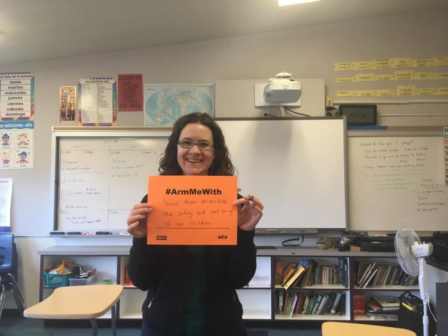 Karen Dorsey, a Woodside Spanish teacher, holds up her #ArmMeWith sign.