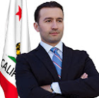 Gubernatorial candidate Klement Tinaj stands in front of the California flag.