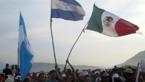 The Honduras and Mexican flag as two parts of the caravan merge