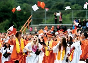 Woodside graduates wear orange and white robes. Credit:  The Almanac