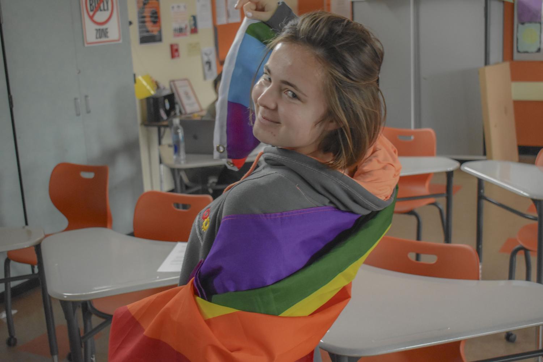 Rachelle Taveau, a Woodside junior, holding a LGBTQ pride flag.