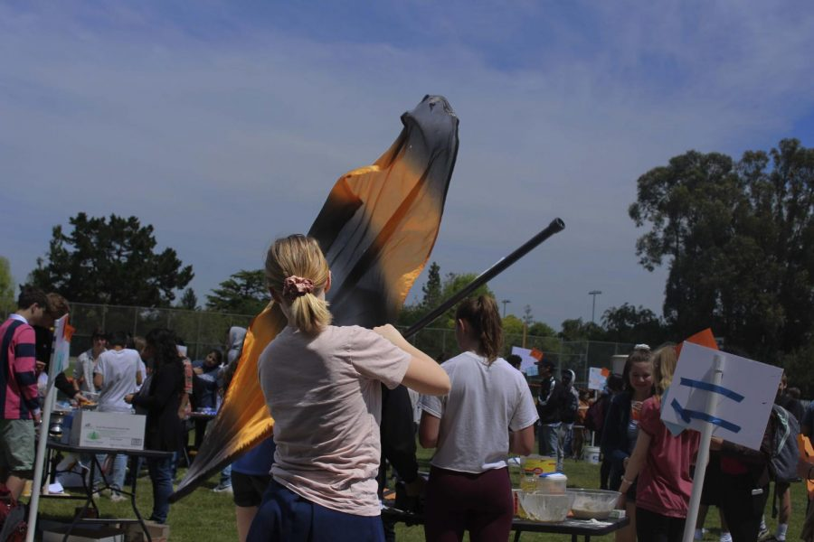 A member of the Color Guard Club twirls a flag.