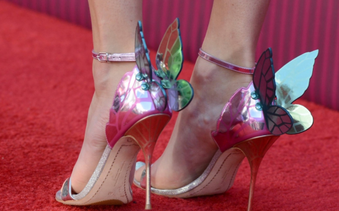 Swift wears colorful butterfly heels to the iHeartRadio Music Awards, hinting at her next era.