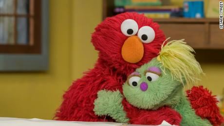 Newest Muppet, Karli, and Elmo embrace on internet-only video.