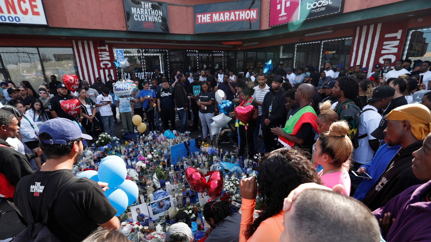 People gather around Nipsey Hussle's store, The Marathon Clothing, in South Los Angeles to pay their respects.