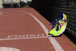A pair of running shoes rest on the finish line at the Woodside High School track.