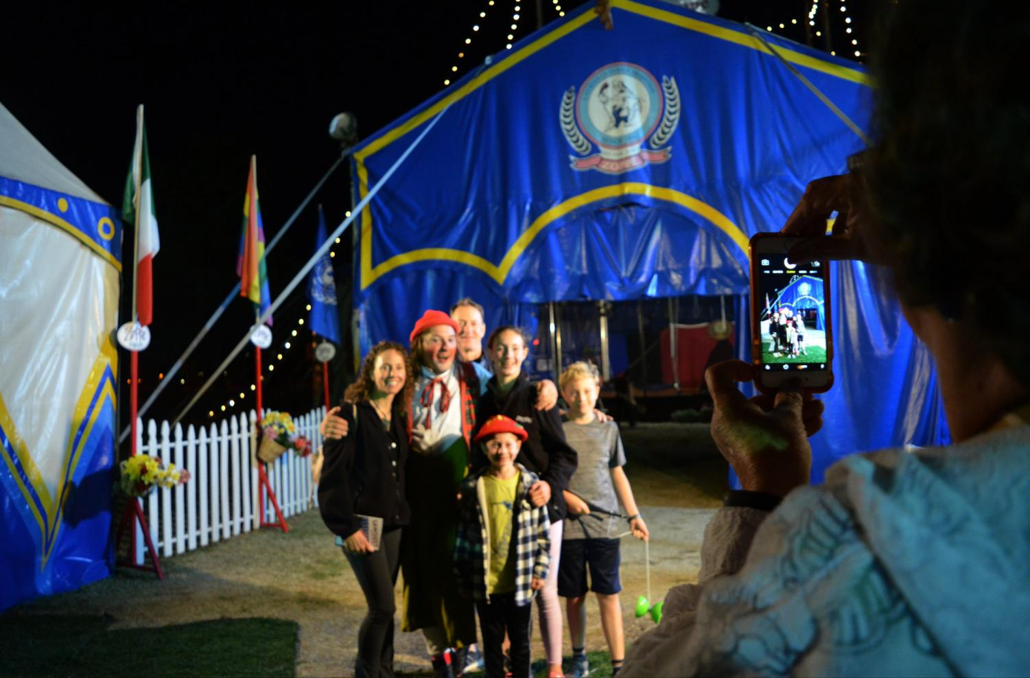 A family takes a picture with director and head clown Giovanni Zoppé outside Zoppé Family Circus's distinctive tent after a show on October 26, 2019.