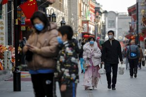 People wearing protective face masks walk on a street in Beijing, Sunday, Feb. 23, 2020. South Korea and China both reported a rise in new virus cases on Sunday, as the South Korean prime minister warned that the fast-spreading outbreak linked to a local church and a hospital in the country