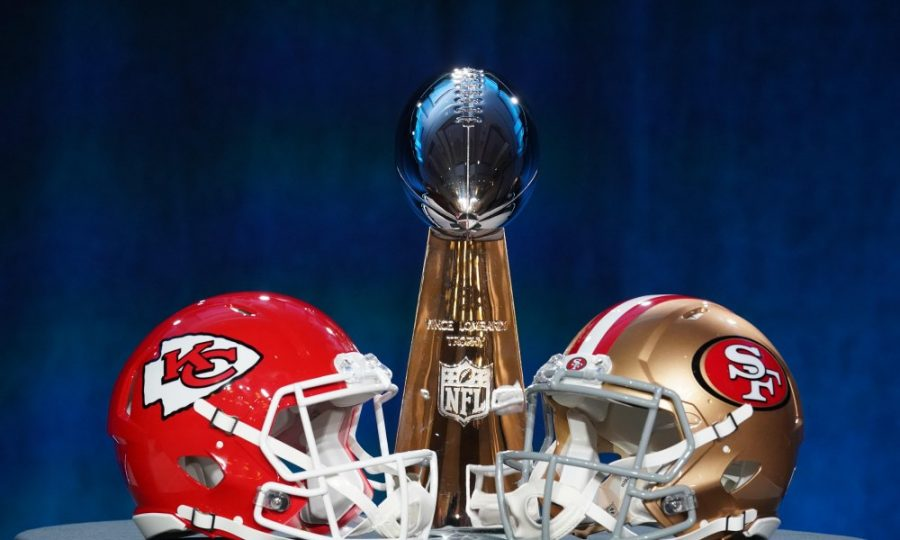 The two teams' helmets line up with the Lombardi Trophy in the background.
