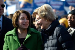 Amy Klobuchar (left) and Elizabeth Warren (right) spoke together before lining up in the Martin Luther King Jr. Day march in Columbia, South Carolina.