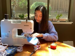 Elise Hadidi, a Woodside sophomore, sews a N95 mask cover at home.