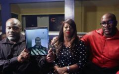 During an interview with CNN, George Floyd's two brothers and cousin hold up a photo of Floyd.