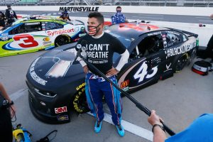 Bubba Wallace stands next to his Black Lives Matter 43 Chevy.