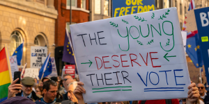 "A student holds up a sign saying ""the young deserve their vote"" at a UK vote march."
