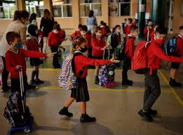 Students in Spain social distance and wear masks as they resume in-person school.