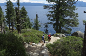 Two people hike down to a beach in Lake Tahoe. They are surrounded by the beauties of nature.