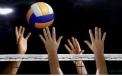 Hands reach out to touch a volleyball first over a net.