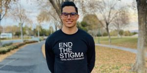 """Robinson stands in the street, smiling, wearing an """"End the Stigma"""" shirt encouraging people to open up about their mental health."""