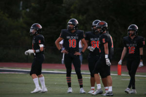 Woodside Quarterback Ben Shepard (number 10) meets with team members during Woodside's game last month against Aragon. Woodside lost its recent game against Cupertino and now has a 3-1 record.